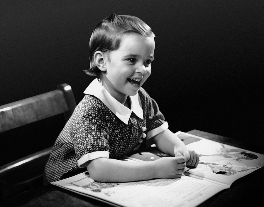 Child Photograph - Smiling Young Girl Reading Book by George Marks