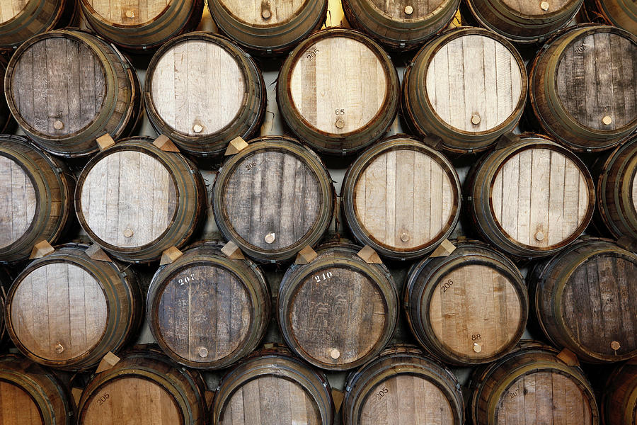 Horizontal Photograph - Stacked Oak Barrels In A Winery by Marc Volk
