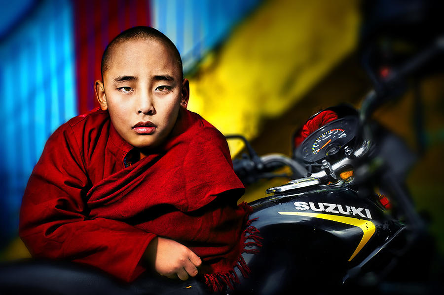 2011 Photograph - The Boy Monk In Red Robe Standing Beside A Motorcycle In A Buddh by Max Drukpa