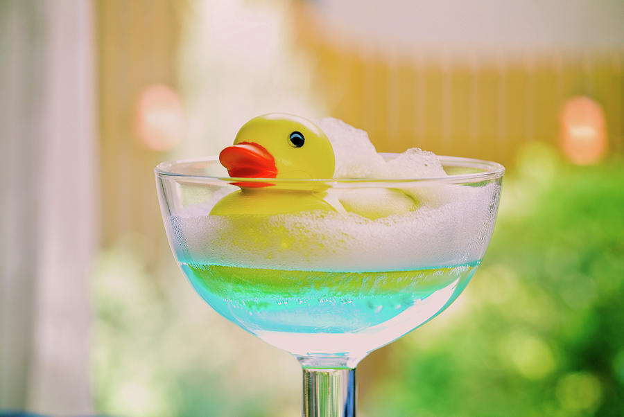 Toy Duck Swimming In A Glass Of Blue Water Photograph by Margarita Komine