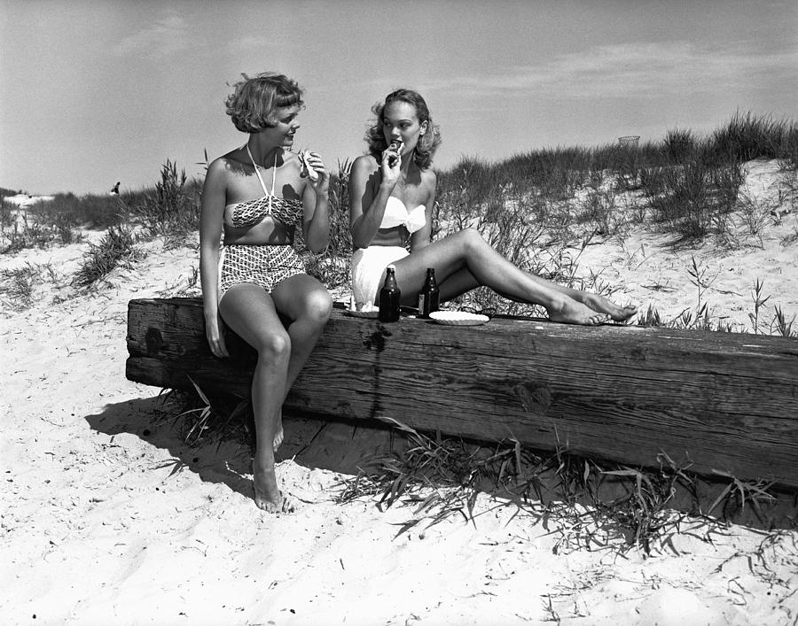 Adult Photograph - Two Women In Bikini Eating Snack On Beach, (b&w) by George Marks