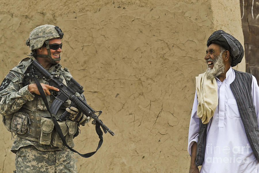 Afghan National Army Photograph - U.s. Army Specialist Talks To An Afghan by Stocktrek Images