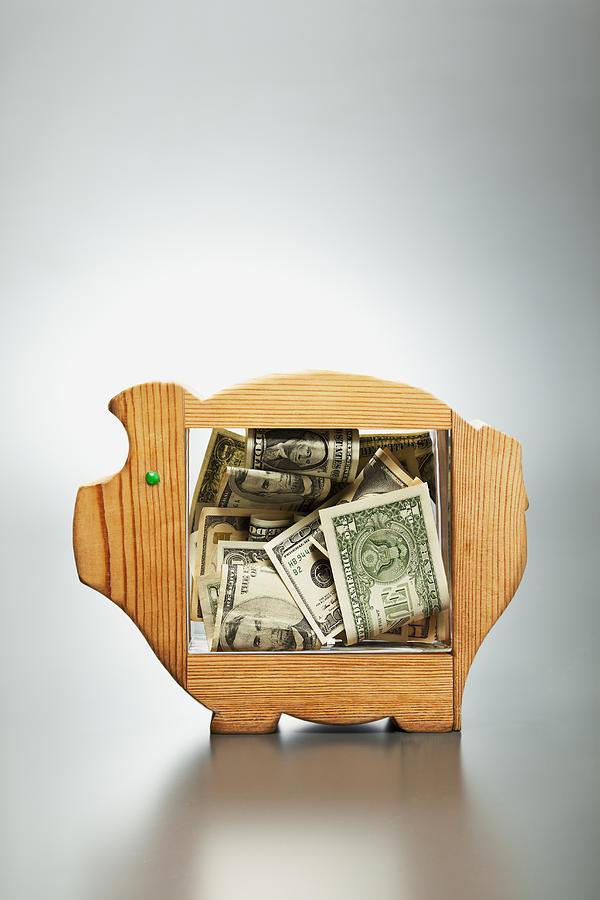 Us Dollar Banknotes In Piggy Bank Photograph by Yuji Sakai