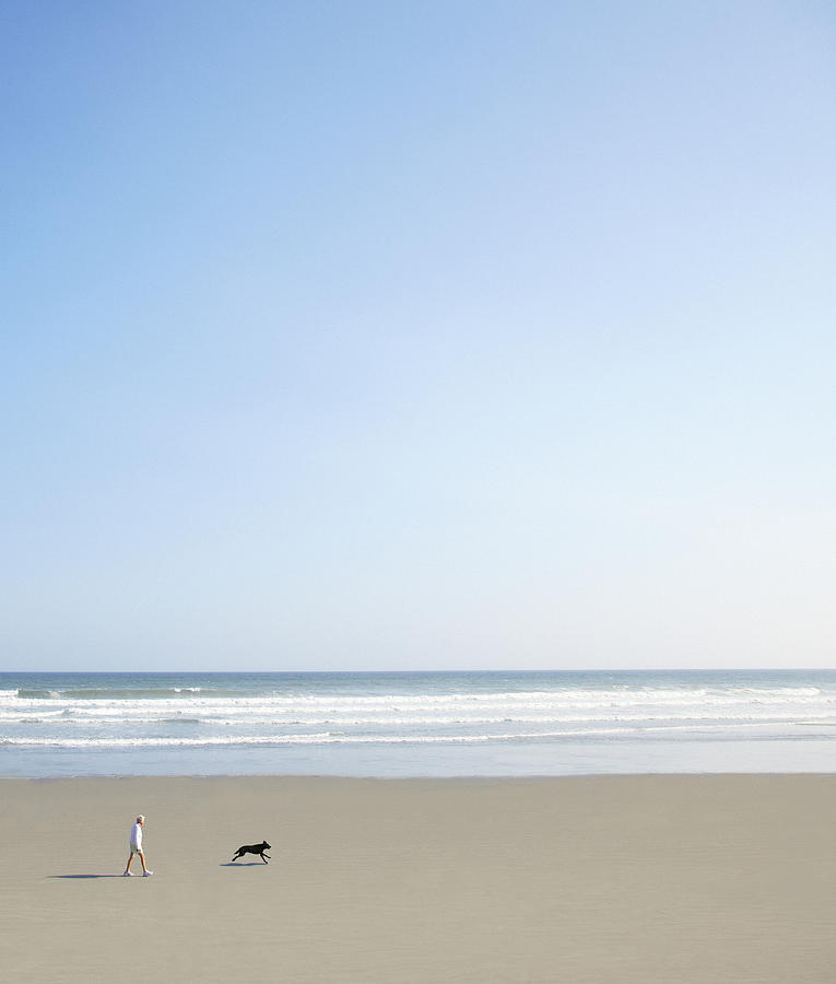 Adult Photograph - Woman And Dog On Beach by Richard Newstead