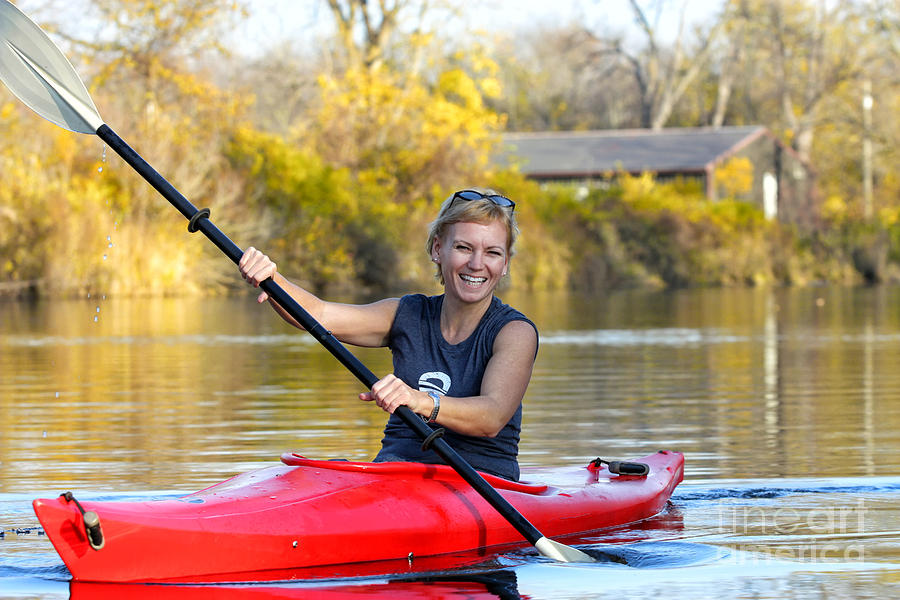 woman kayaking on michigan river in autumn photograph by christopher