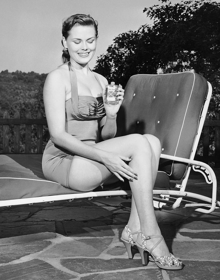 Adult Photograph - Woman On Lawn Chair Applying Oil To Her Legs by George Marks