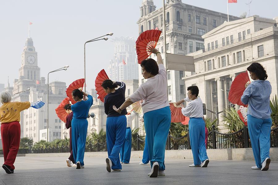 Adult Photograph - Women Practising Tai Chi With Fans On The Bund by John Banagan