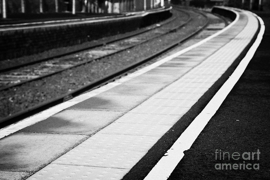 Railway Photograph - Yellow Warning Line And Textured Contoured Tiles Railway Station Platform And Track Northern Ireland by Joe Fox