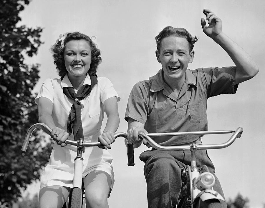 Adult Photograph - Young Couple Riding Bicycles by George Marks