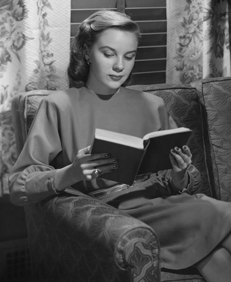 Adult Photograph - Young Woman Sitting On Sofa, Reading Book, (b&w) by George Marks