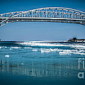 Blue Water Bridges With Reflection And Ice Flow by Ronald Grogan