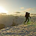 A Man Backcountry Skiing At Sunset by Kennan Harvey