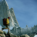 A Man Backpacks In Front Of Fitz Roy by Ty Milford