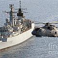 A Royal Navy Merlin Helicopter Passes Over Hms Cumberland by Paul Fearn