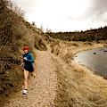 A Woman Jogging On A Dirt Trail by Jordan Siemens