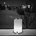 candle in the window looking out over snow covered scene in small rural village of Forget Saskatchew by Joe Fox