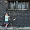 Girl Standing Next To Brick Wall by Jennifer Huls