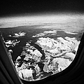 Looking Out Of Aircraft Window Over Snow Covered Fjords And Coastline Of Norway Europe by Joe Fox