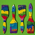 Multicolored Paint Brushes On Green Background by Jim Corwin
