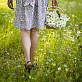 Woman Walking Through A Wild Flower Meadow With A Basket Of Flow by Lee Avison