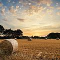 Stunning Summer Landscape Of Hay Bales In Field At Sunset by Matthew Gibson