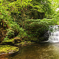 Stunning Waterfall Flowing Over Rocks Through Lush Green Forest  by Matthew Gibson