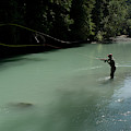 A Man Casts In A River Wearing Waders by Alain Denis