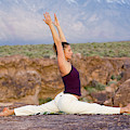 A Woman Practicing Yoga On A Dry Lake by Lars Schneider