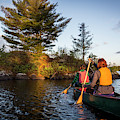 A Young Couple Paddles A Canoe On Long by Jerry Monkman