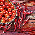 Basket Of Ripe Cherry Tomatoes And Dried Red Chillies On Rustic  by Ken Biggs