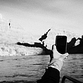 man taking photos with smartphone during boat ride along the colorado river in the grand canyon Ariz by Joe Fox