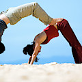 A Man And Woman Practicing Yoga by Lars Schneider