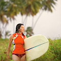 A Woman Carries A Surfboard To The Beach by Ty Milford