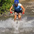 A Woman Mountain Bikes Along Trail 401 by J.C. Leacock