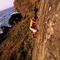 A Man Is Bouldering Near The Ocean by Bennett Barthelemy