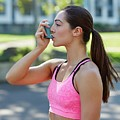 Young Woman Using Inhaler by Science Photo Library