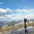 A Backpacker Stands Atop A Mountain by Bud Force
