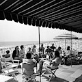 A Group Of People On A Terrace Overlooking by Tom Leonard