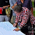 A Lady Signs Petition At May Day Rally Singapore by Imran Ahmed