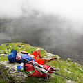 A Male Hiker Is Resting In A Grassy by Menno Boermans