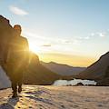 A Man Hiking On Snowfield At Sunrise by Kennan Harvey