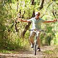 A Man Rides A Bicycle by Corey Rich