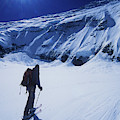 A Man Ski Touring Under Blue Skies by Jimmy Chin