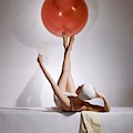 A Model Balancing A Red Ball On Her Feet by Horst P Horst