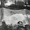 A Model Lying On A Hammock by Gene Moore