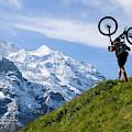 A Mountain Biker Is Carrying His Bike by Menno Boermans
