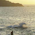 A Person Hiking On Rocky Shore by Chris Giles