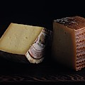 A Variety Of Cheese On A Cutting Board by Romulo Yanes