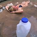 A Water Jug Near A Woman Soaking by Corey Rich