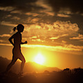 A Woman Jogs Under Sunset by Christian Pondella